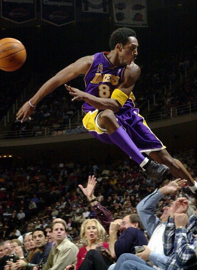 Kobe Bryant na snímku z roku 2001 skáče při jedné z herních situací mezi fanoušky.