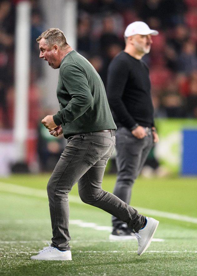 Trenér Sparty Praha Pavel Vrba oslavuje vítězství 1:0 nad Slavií, jeho protějšek Jindřich Trpišovský je za ním zasmušilý.