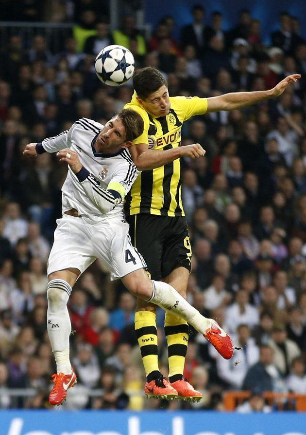 Kanonýr Borussie Dortmund Robert Lewandowski (vpravo) ve vzdušném souboji se zadákem Realu Madrid Sergiem Ramosem.