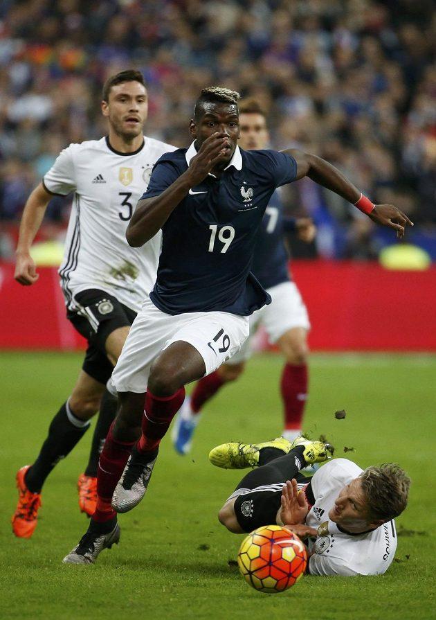 Z přípravy Francie - Německo v Paříži. Domácí středopolař Paul Pogba obchází ležícího Bastiana Schweinsteigera.