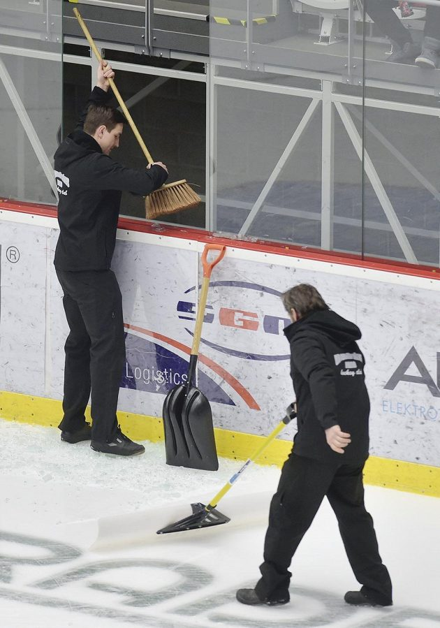Pořadatelé v Třinci uklízejí střepy poté, co vítkovičtí hráči při rozbruslení rozbili jedno z ochranných tvrzených skel za brankou.