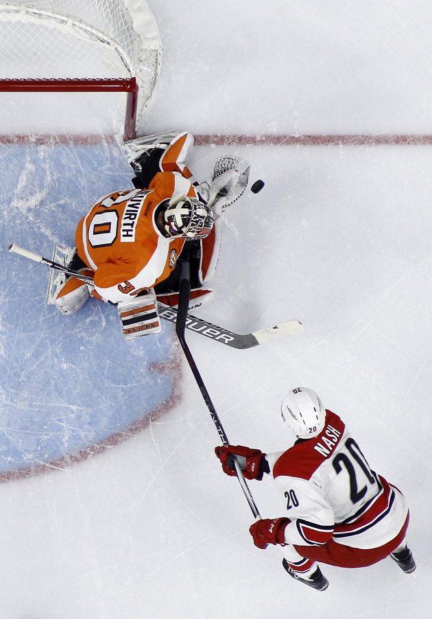 Brankář Philadelphie Flyers Michal Neuvirth při zákroku proti Riley Nashovi z Caroliny.
