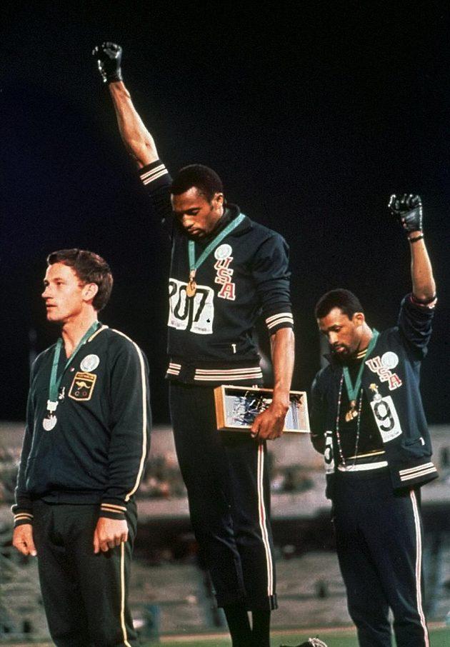 Američtí atleti Tommie Smith (uprotřed) a John Carlos - zlatý a bronzový běžec na 200 m při OH v Mexiku - na stupních vítězů při protestu proti rasismu ve své zemi.