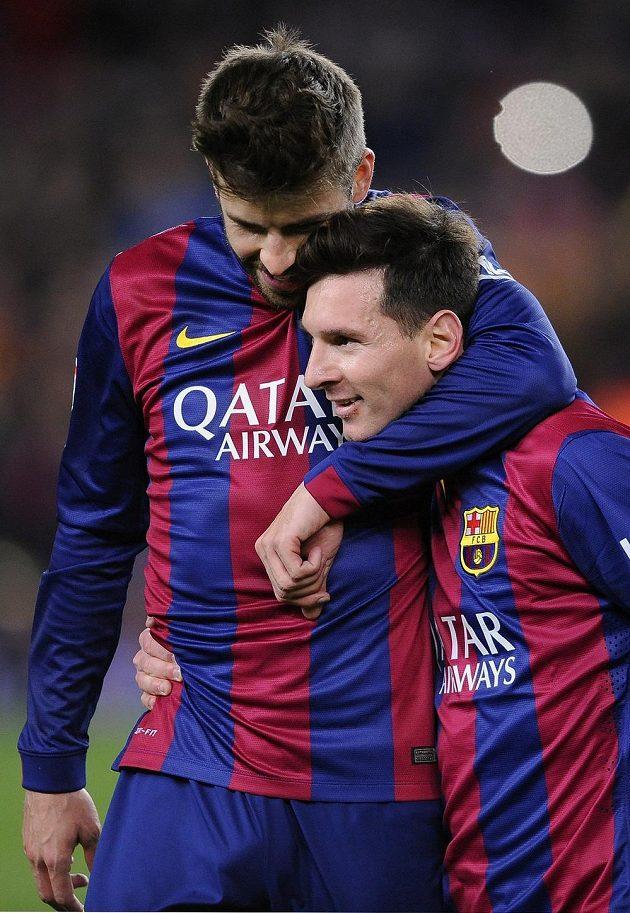 Obránce Barcelony Gerard Pique a útočník Lionel Messi se radují z výhry 2:1 v ostře sledovaném derby nad Realem Madrid.