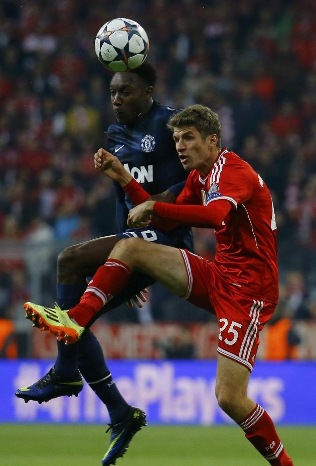 Thomas Müller z Bayernu Mnichov (v červeném dresu) v hlavičkovém souboji s útočníkem Rudých ďáblů Dannym Welbeckem.