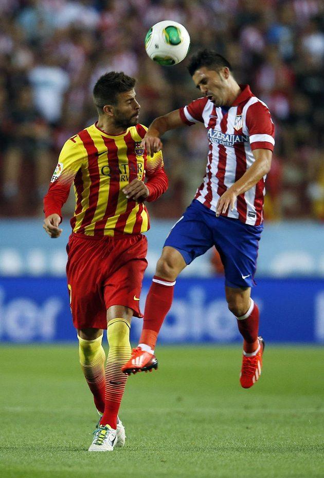 Gerard Piqué z Barcelony (vlevo) v hlavičkovém souboji s Davidem Villou.