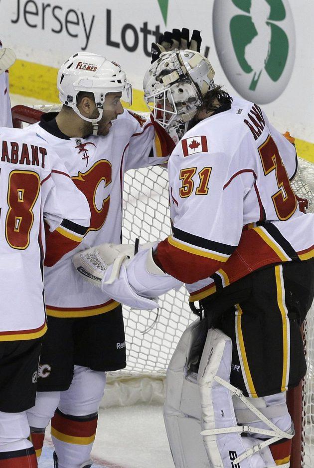 Brankář Calgary Karri Rämö slaví se spoluhráčem Markem Cundarim výhru v New Jersey.