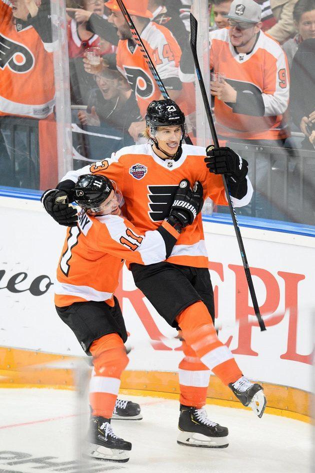 Hokejisté Philadelphie Travis Konecny (vlevo) a Oskar Lindblom oslavují gól během utkání NHL s Chicagem.