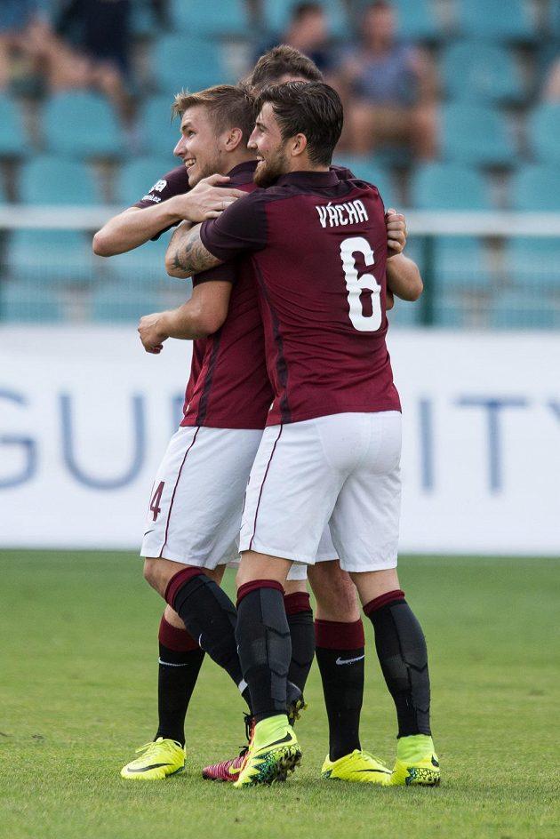 Martin Frýdek (vlevo) přijímá od sparťanských spoluhráčů gratulace k jednomu ze svých gólů proti Dukle.