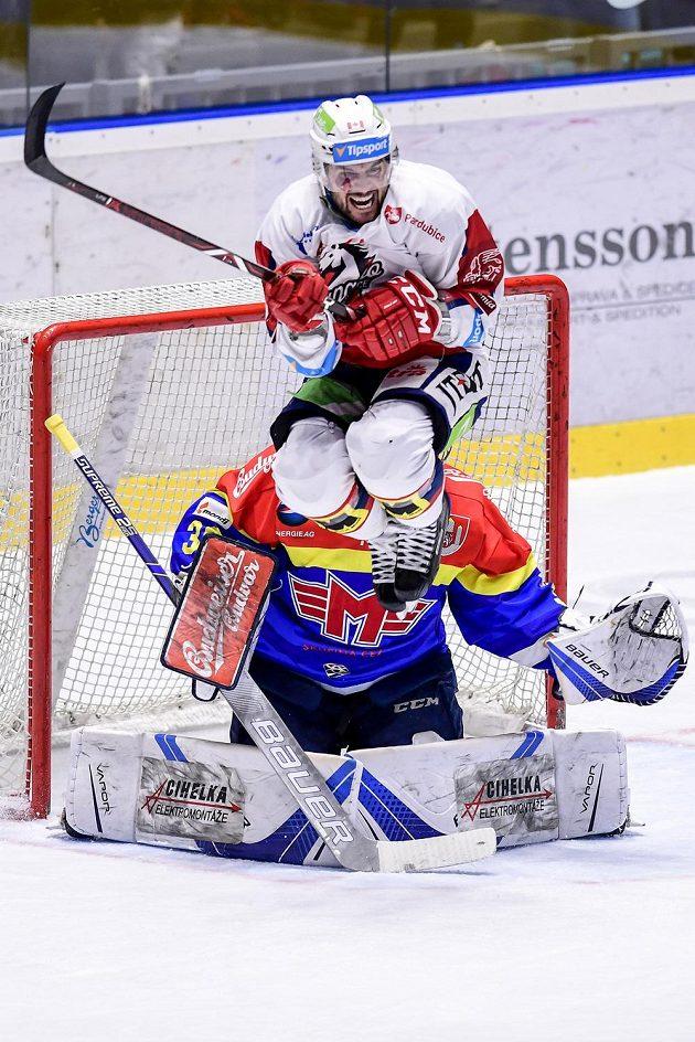 Brian Ihnačák (ve výskoku) z Pardubic a brankář Budějovic Petr Kváča během utkání baráže o hokejovou extraligu.