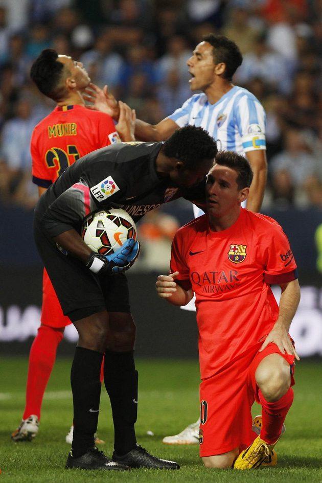 Zatímco brankář Málagy Carlos Kameni zvedá z trávníku Lionela Messiho, obránce Weligton Oliveira v pozadí atakuje dalšího útočníka Barcelony Munira El Haddadiho.