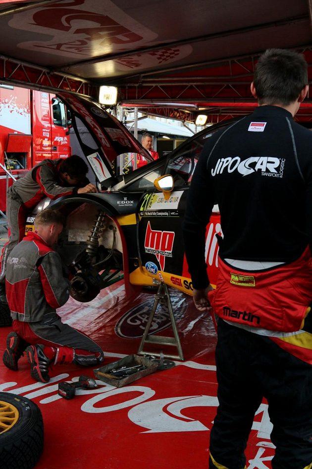 Martin Prokop sleduje mechaniky při práci na jeho Fordu Fiesta WRC během Italské rallye.