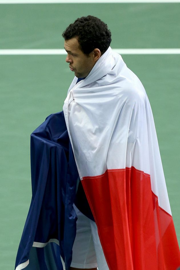 Jo-Wilfried Tsonga s francouzskou vlajkou po vítězství nad Jiřím Veselým ve čtvrtfinále Davisova poháru.