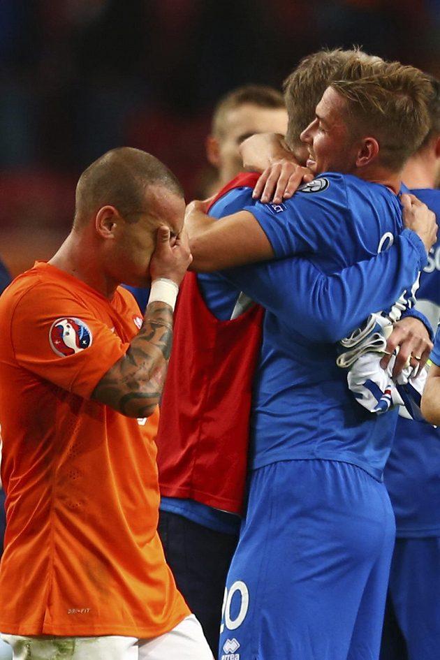 Nizozemský záložník Wesley Sneijder si zakrývá oči před slavícími fotbalisty Islandu.