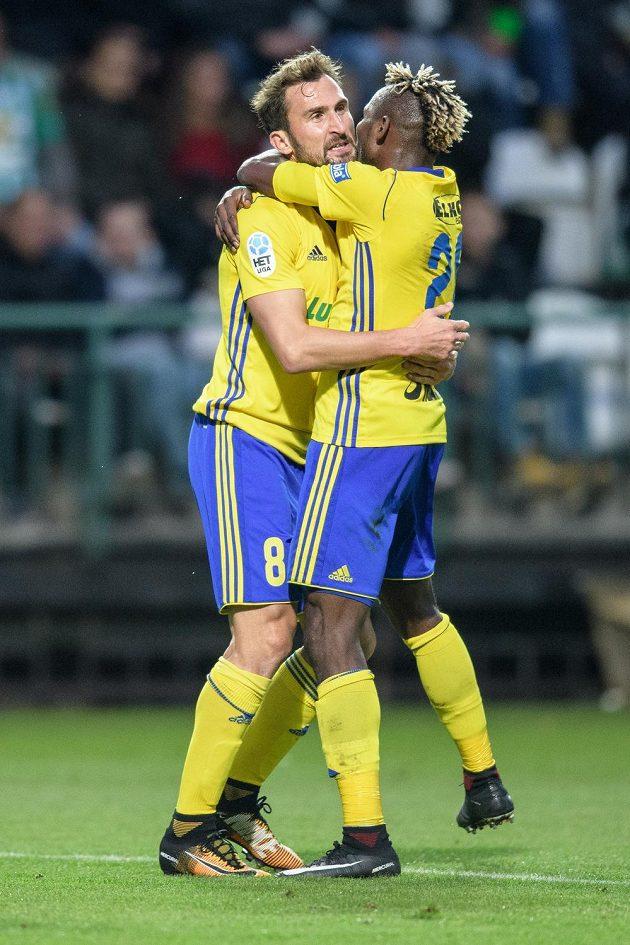 Fotbalisté Zlína Petr Jiráček (vlevo) a Mosses Ekpai oslavují vedoucí gól na Bohemians.