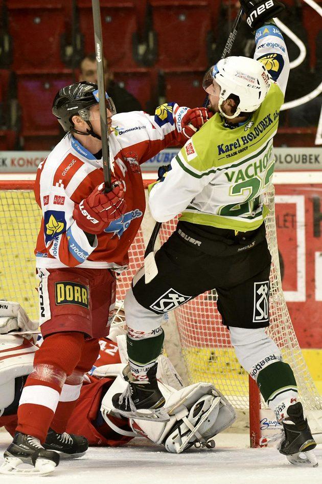 Zleva obránce Olomouce Jiří Ondrušek a karlovarský útočník Michal Vachovec, dole na ledě je olomoucký brankář Branislav Konrád.
