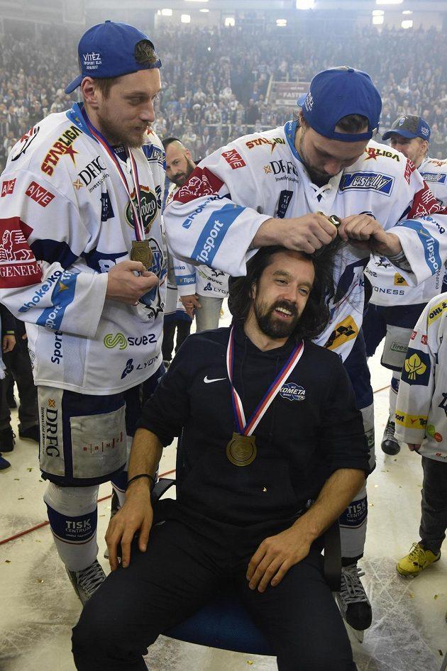 Ondřej Němec z Brna stříhá po zisku titulu kondičního trenéra Komety Miloše Pecu, který prohrál sázku. Vlevo je Marcel Haščák. Kometa Brno vyhrála hokejovou extraligu.