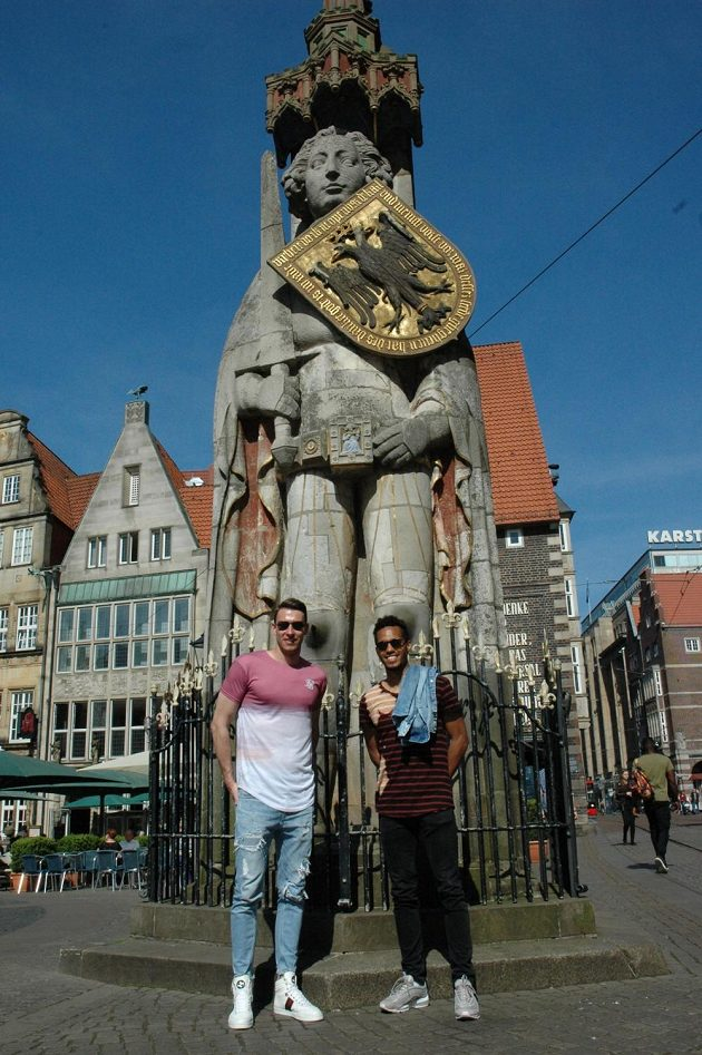 Brankář Jiří Pavlenka (vlevo) a Theodor Gebre Selassie u sochy rytíře Rolanda v centru Brém.