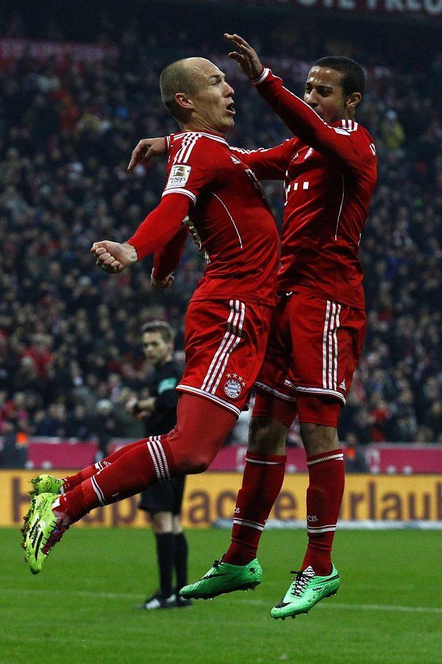 Fotbalisté Bayernu Arjen Robben a Thiago (vpravo) slaví gól nizozemského záložníka proti Schalke 04.