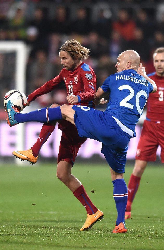 Český fotbalista Jaroslav Plašil (vlevo) v souboji s Emilem Hallfredssonem z Islandu.