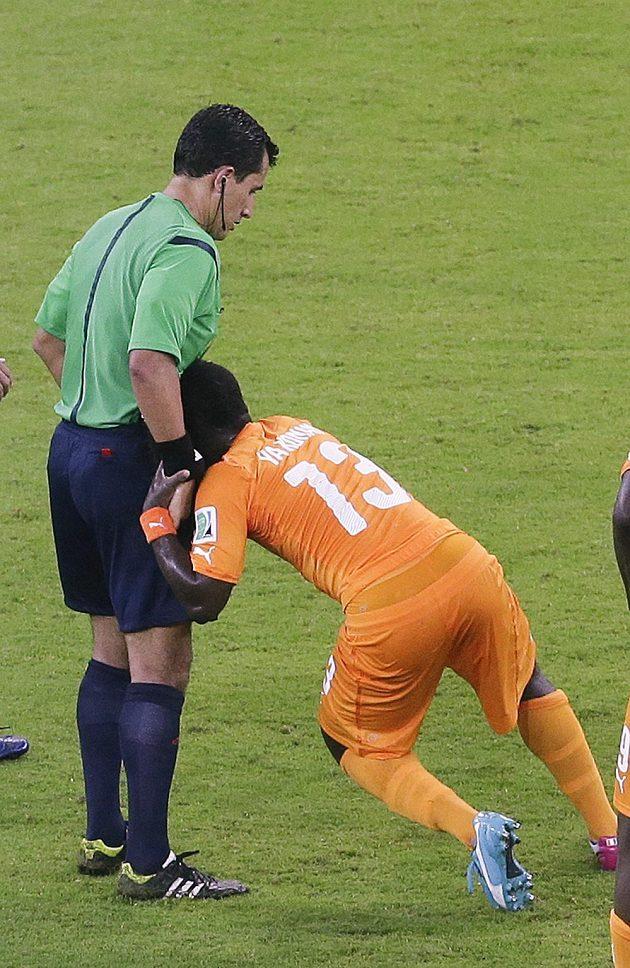Rozhodčí Enrique Osses pomáhá vstát Ya Konanovi z Pobřeží slonoviny.