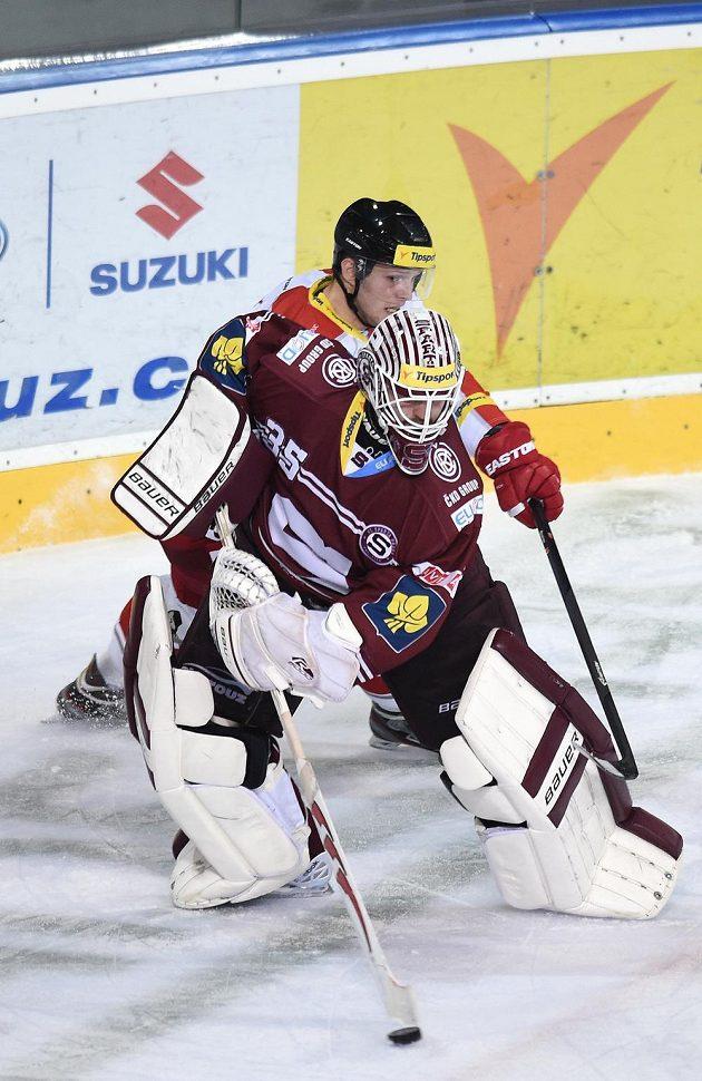 Sparťanský brankář Filip Novotný odehrává puk v duelu s Olomoucí.