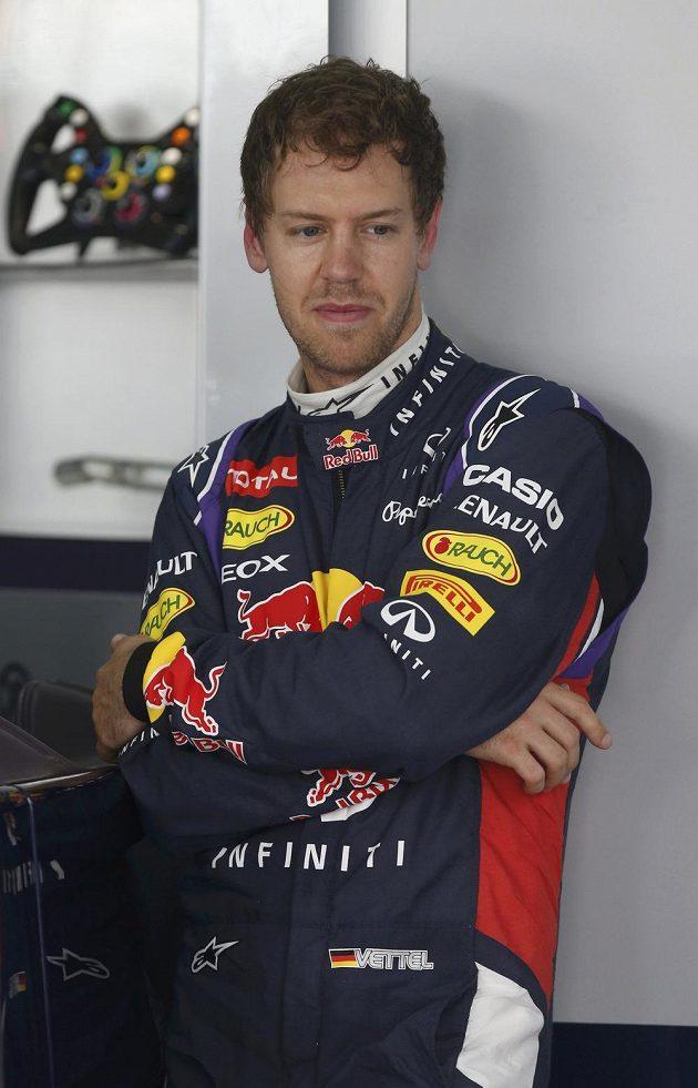 Zamyšlený Sebastian Vettel vyčkává v garáži Red Bullu při měřeném tréninku v Sepangu.