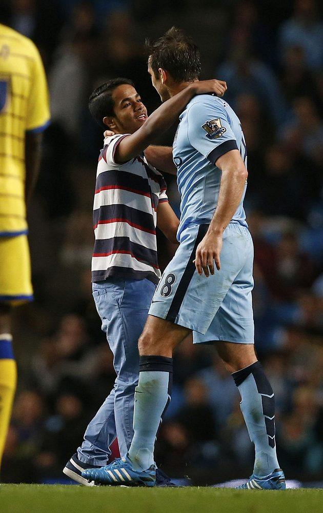 Jeden z mladých příznivců se snaží obejmout se záložníkem Manchesteru City Frankem Lampardem během utkání s Sheffieldem.
