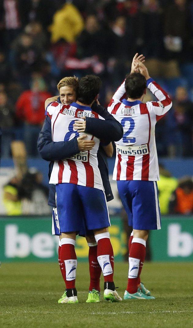 Fotbalisté Atlétika Madrid slaví vítězství nad Realem. Zleva útočník Fernando Torres, střelec prvního gólu Raúl García a stoper Diego Godín.
