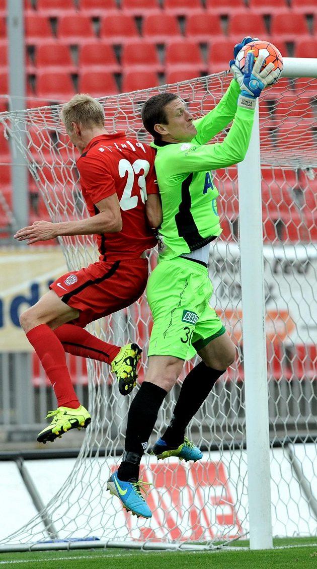 Teplický gólman Tomáš Grygar (vpravo) stahuje míč před brněnským Michalem Škodou.