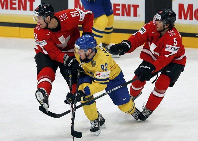 Švédský útočník Gabriel Landeskog (ve žlutém dresu) se probíjí přes švýcarské hráče.