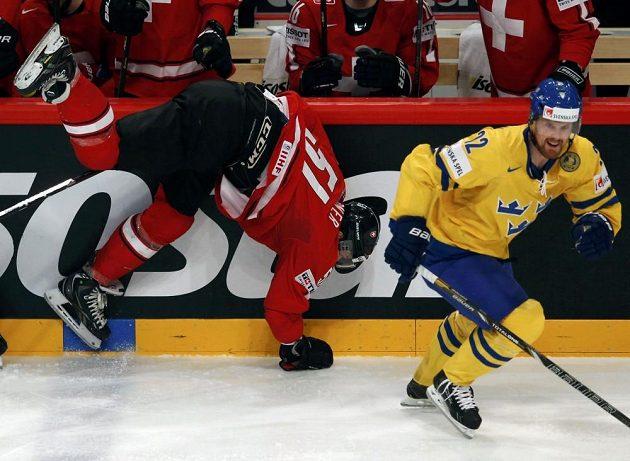 Švýcar Ryan Gardner padá u mantinelu, vpravo bruslí švédský útočník Daniel Sedin.