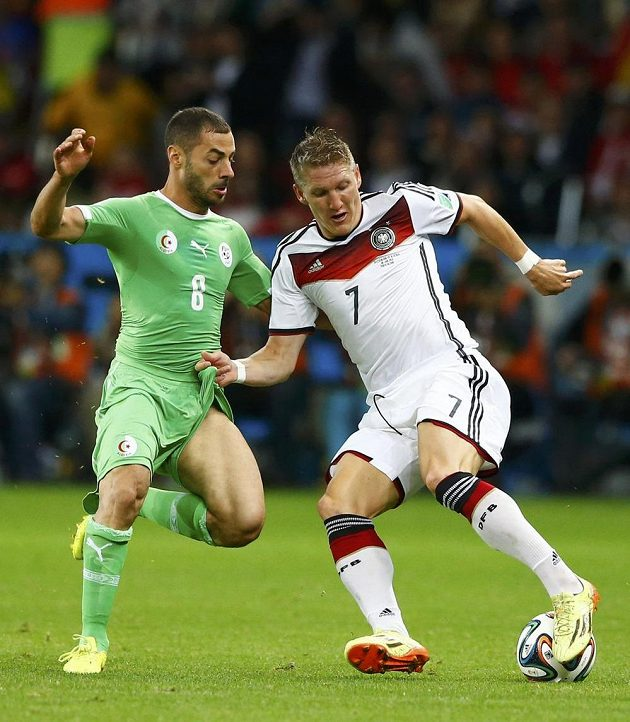 Bastian Schweinsteiger bojuje o míč s Mahdím Lasínem z Alžírska.