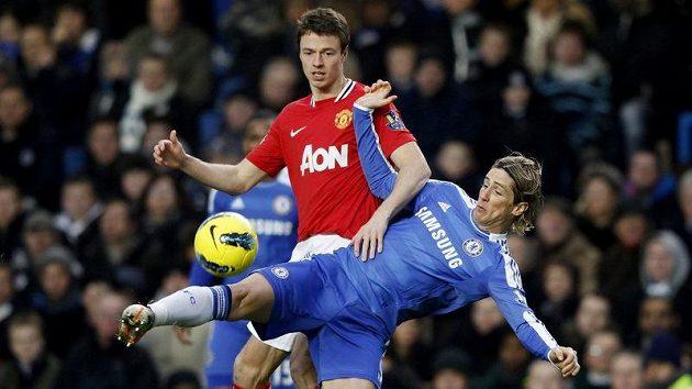 Fernando Torres z Chelsea padá v souboji s Jonny Evansem z Manchesteru United.