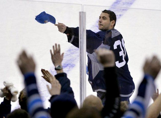 Nám taky, prosím! Brankář Ondřej Pavelec rozhazuje klubové čepice po hokeji vyhladovělým fanouškům Winnipegu...