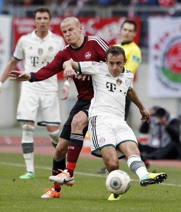 Adam Hloušek z Norimberku (v červeném) v souboji s Rafinhou z Bayernu Mnichov.