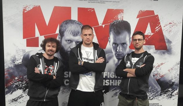 Trenér Dan Barták (vlevo), Viktor Pešta a vpravo Šimon Pešta v Rusku před billboardem.