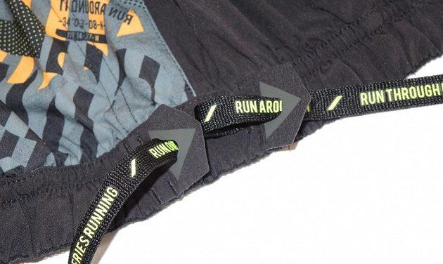 Běžecké trenýrky Reebok Running Graphic Board Short: detail vyztužení výstupů šňůrky.