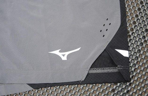 Běžecké trenky Mizuno Aero 4.5 Short - detail rozparku a reflexního loga.