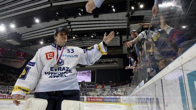 Brankář Vítkovic Jakub Štěpánek se stříbrnou medaili na krku zdraví fanoušky svého týmu.