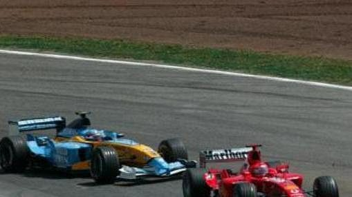 Fernando Alonso na renaultu (vlevo) stíhí ferrari Michaela Schumachera (vpravo) a Rubense Barrichella.