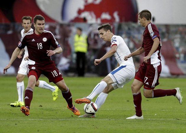 David Pavelka vyšívá kličky mezi lotyšskými obránci.