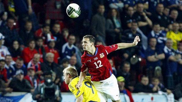 Zdeněk Pospěch (vpravo) uklízí míč do bezpečí před Skotem Naismithem.