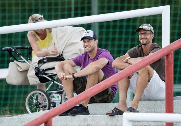 Vykartovaní fotbalisté Bohemians Tomáš Fryšták (uprostřed) a Michal Šmíd sledují utkání na Dukle.