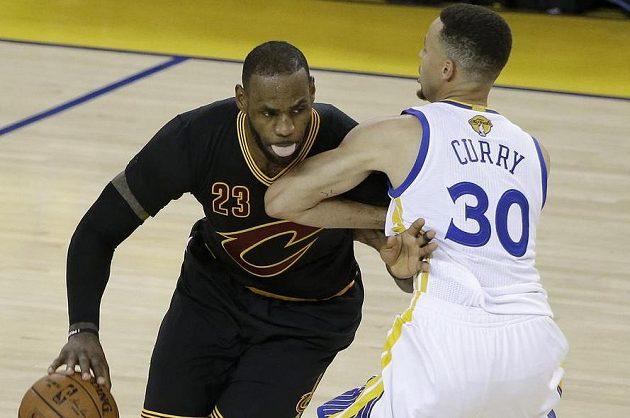 LeBron James (vlevo) z Clevelandu se snaží obejít hvězdu soupeře Stephena Curryho z Golden State.