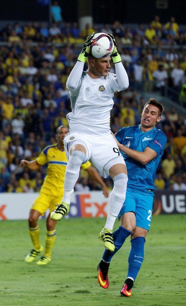 Slovák Róbert Mak z Petrohradu v souboji s brankářem Predragem Rajkovičem z Maccabi Tel Aviv.