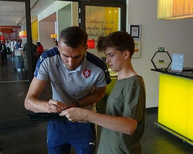 Útočník Tomáš Chorý se podepisuje jednomu z lovců autogramů po příjezdu české fotbalové reprezentace do 21 let na ME do Polska.
