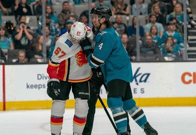 Český útočník Calgary Flames Michael Frolík čelí útoku obránce San Jose Sharks Brendena Dillona (4) během utkání NHL.