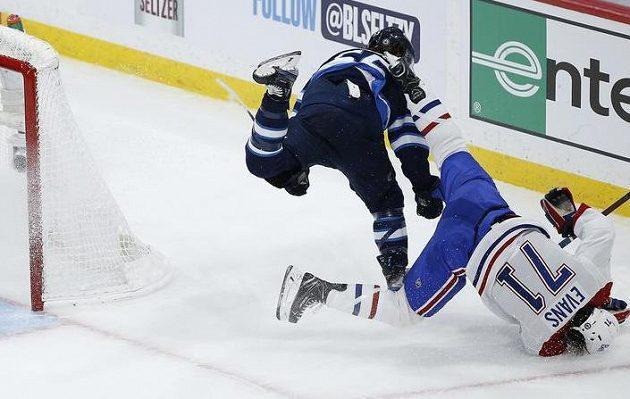 Útočník Winnipegu Jets Mark Scheifele (55) srazil Jakea Evanse (71) z Montrealu Canadiens během utkání 2. kola play off NHL.