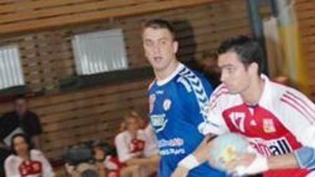 Český házenkář David Juříček přechází přes jednoho zhráčů soupeře.